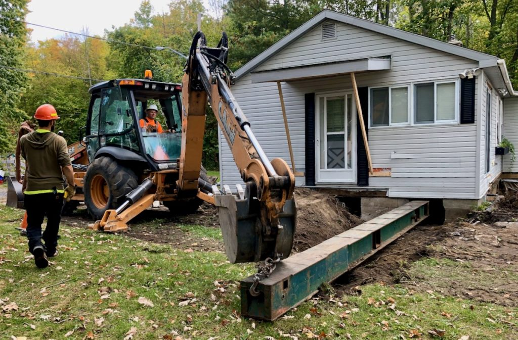 Installing steel beams with backhoe under house through hole in foundation