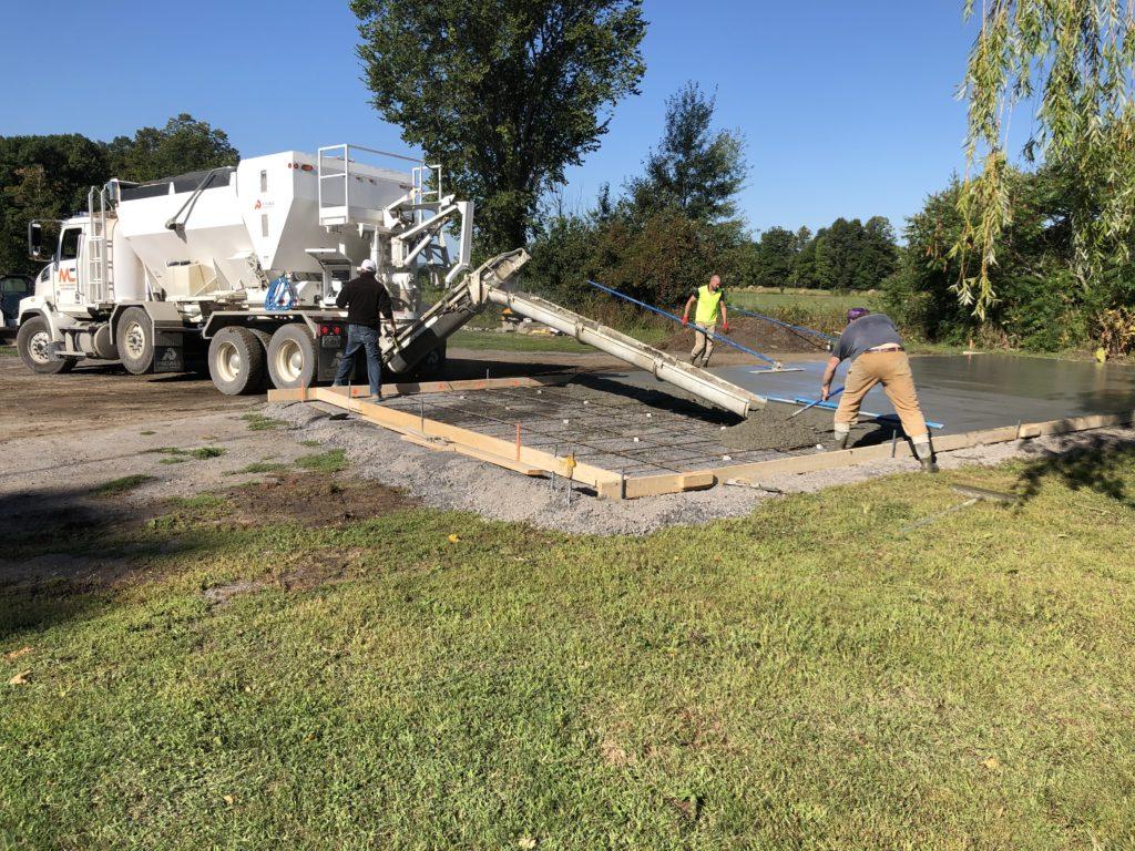 construction crew pouring concrete slab